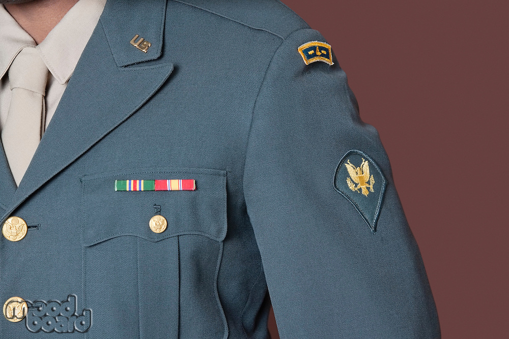 Close-up of US military officer's uniform with badge over brown background