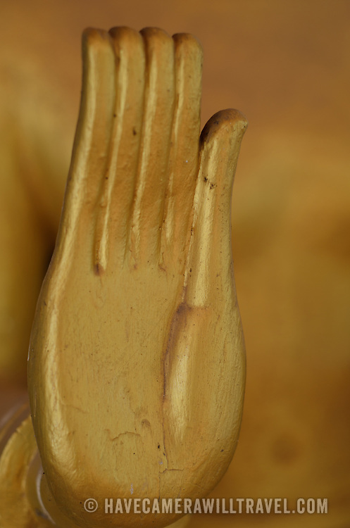 Close-up of the golden hand on a statue of The Buddha (Siddhartha Gautama) at a Wat in Vientiane, Laos.