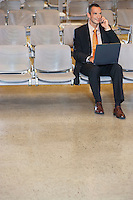 Business man using mobile phone and laptop in airport lobby