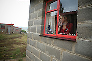 (Bobete, Lesotho - February 7, 2008) Dr. Jen Furin, Country Director for Partners In Health for Lesotho, makes a cell phone call from inside the PIH home at the clinic in Bobete, during an afternoon rain storm. .Staff Photo Justin Ide/Harvard University News Office