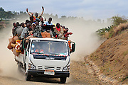 An Isuzu truck filled to the brim with people, cargo, and several chickens travels down a dirt road. Isuzu trucks are a common mode of public transportation in southern Ethiopia. (Konso, Ethiopia - August 9, 2010)