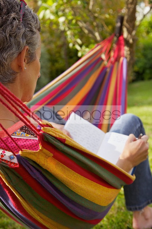 Back View of Woman on Hammock Reading