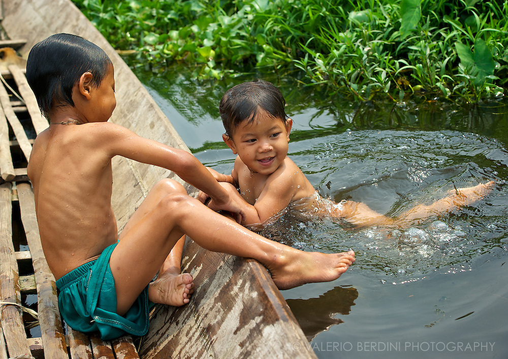 Children enjoy a swim amid the canal to reach a boat.