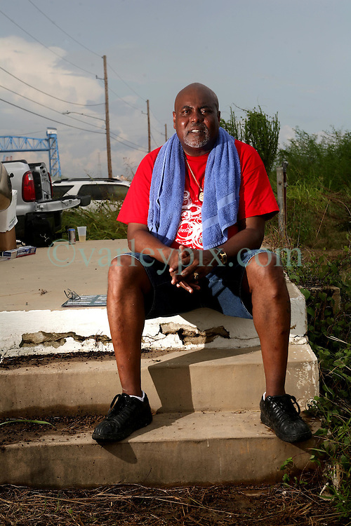 29 August 2007. Lower 9th Ward, New Orleans, Louisiana. <br /> Second anniversary of Hurricane Katrina. Jason Freeman sits on the steps of 1837 Jordan Ave in the Lower 9th Ward. The steps are all that remain of his house after it was deluged by the levee breach just  a block from the steps. He has gathered with friends and family for a BBQ to remember those who perished in the terrible flooding.  Jason hopes to rebuild. Many residents are struggling to return to the still derelict and decimated Lower 9th Ward.<br /> Photo credit©; Charlie Varley/varleypix.com