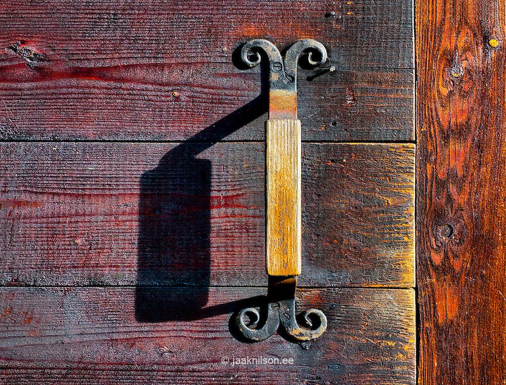 Old handle on wooden scratched door. Close-up of grip, doorhandle.