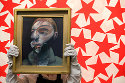 "© Licensed to London News Pictures. 21/06/2019. London, UK. A technician holds Francis Bacon's ""Self-Portrait"", 1975 (Est £15m- £20m) in front of Charline von Heyl's Cluster 2015 (Est £50,000 - £70,000) at the preview of Summer Contemporary Art Auctions at Sotheby's George Street, London. Photo credit: Dinendra Haria/LNP"