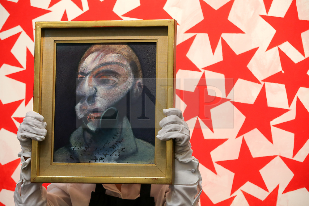 """© Licensed to London News Pictures. 21/06/2019. London, UK. A technician holds Francis Bacon's """"Self-Portrait"""", 1975 (Est £15m- £20m) in front of Charline von Heyl's Cluster 2015 (Est £50,000 - £70,000) at the preview of Summer Contemporary Art Auctions at Sotheby's George Street, London. Photo credit: Dinendra Haria/LNP"""
