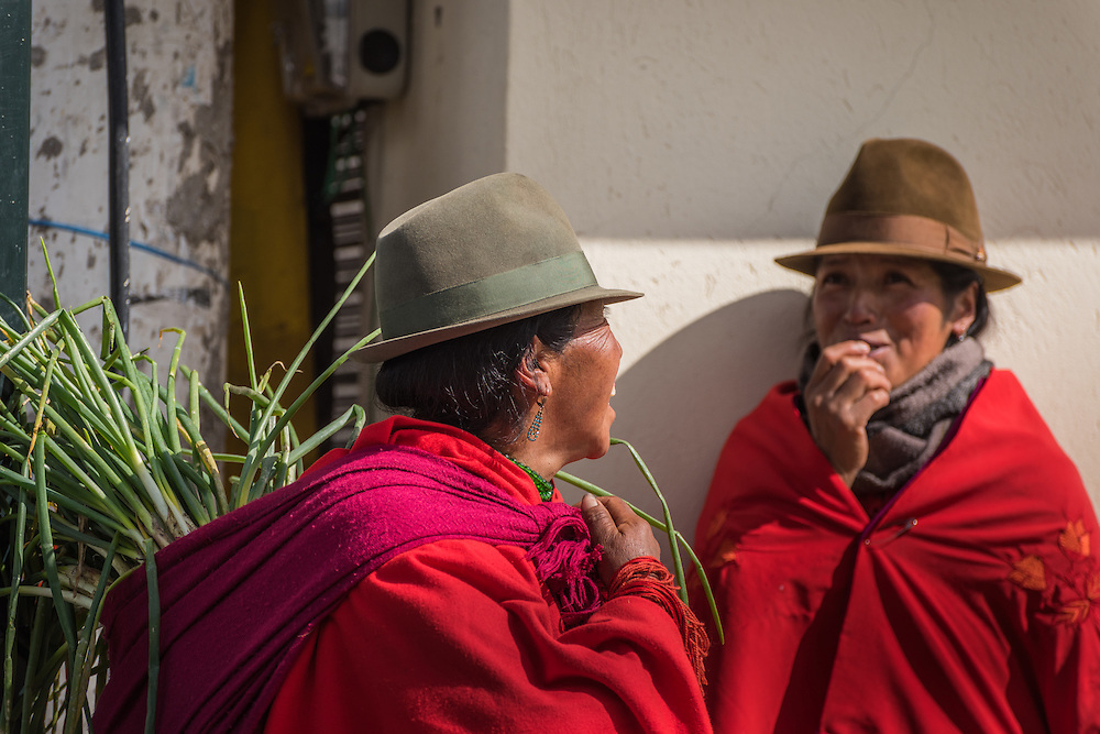 Two woman with red scarfs lauging at each other at the vegetable market, Zumbahue, Ecuador.