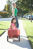 Mother pulling daughter in trolley