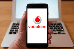 Using iPhone smartphone to display logo of Vodafone mobile phone operator