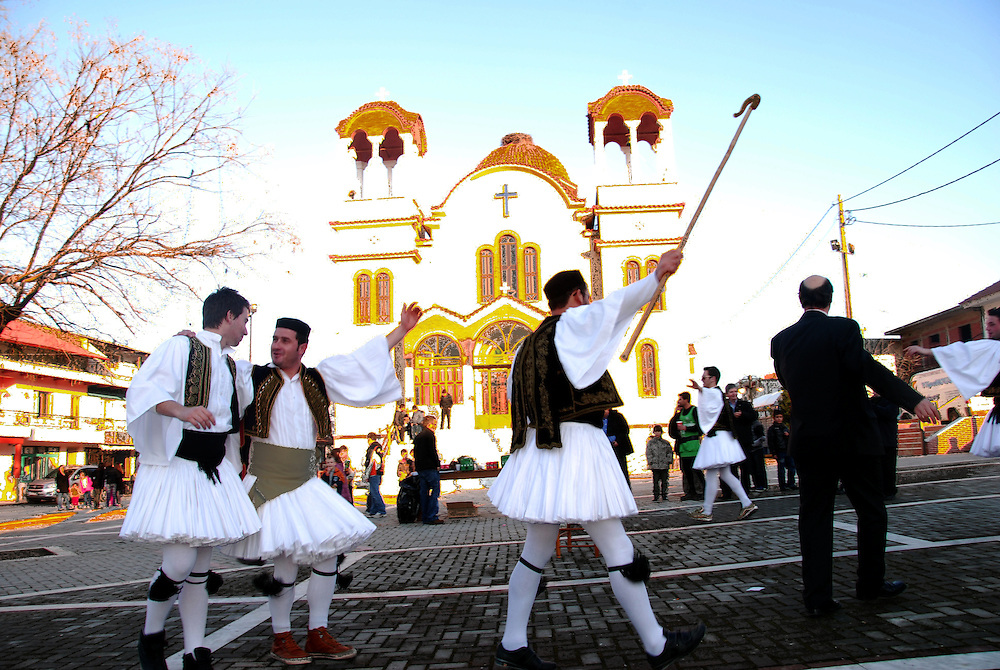 "Men dressed, on January 1st , each as a ""tsolias"" (Greek traditional costume) with the church of Prophet Elias in the background at Drymos village. Thessaly region, central Greece."