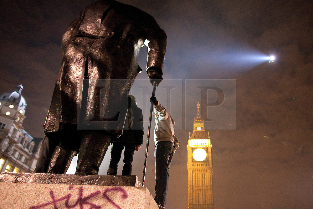 © under license to London News Pictures. 9/12/2010. Protesters on the Churchill Statue in Parliament Square, London, are lit up by the lights of a police helicopter. On the day that MPs vote on tuition fees, 1000s demonstrated in London against a proposed rise in fees and cuts in support.