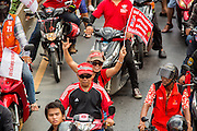 "10 DECEMBER 2012 - BANGKOK, THAILAND:  A Red Shirt protestor on a motorcycle on Petchaburi Rd in Bangkok near the offices of the ruling Pheu Thai party Monday to call for constitutional reform. The Thai government announced on Monday, which is Constitution Day in Thailand, that will speed up its campaign to write a new charter. December 10 marks passage of the first permanent constitution in 1932 and Thailand's transition from an absolute monarchy to a constitutional monarchy. Several thousand ""Red Shirts,"" supporters of ousted and exiled Prime Minister Thaksin Shinawatra, motorcaded through the city, stopping at government offices and the offices of the Pheu Thai ruling party to present demands for a new charter.        PHOTO BY JACK KURTZ"