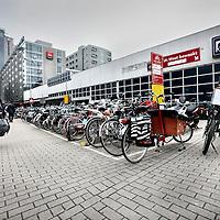 Nederland, amsterdam , 21 juli 2011..De speciale vakken die aangebracht zijn voor scooters en bakfietsen bij het centraal station gaan verdwijnen..De paktijk wijst uit dat normale fietsen ook op deze plekken parkeren waardoor bakfietsen uiteindelijk buiten of half buiten de vakken moeten parkeren..Bicycle parking at the central station in Amsterdam.