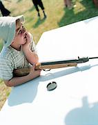 Adolescent au stand de tir à la carabine. Fête foraine de Ville-le-Marclet, Picardie, France. 21.06.2002.