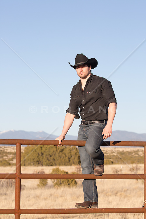 Rugged good looking cowboy on a ranch fence with mountain views