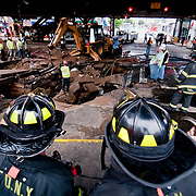 June 14, 2009 - Bronx, NY : Construction crews and emergency workers work to clean up and restore services to the intersection of Broadway and W. 231st St. where a water main broke overnight, leaving much of the community without water, and much of the neighborhood under water.  Two firefighters survey the damage.