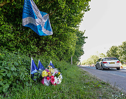 Family and friends of the driver who died after his vehicle was involved in a horror accident early on Saturday morning after a stolen car went on the wrong side of the road have laid flowers and Scottish flags at the scene.<br /> <br /> &copy; Dave Johnston / EEm