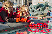 Vita Wooolfe, 6 3/4 (fur lined hood), and Orban O'Brien, 9, push a wreath into the fountain - Silence in the Square oraganised by the British Legion in Trafalgar Square  - 11 November 2016, London.