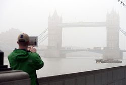 © Licensed to London News Pictures. 01/03/2012. A man takes a picture of Tower Bridge with an iPad. Fog in Central London this morning 2nd March 2012.  Photo credit : Ben Cawthra/LNP