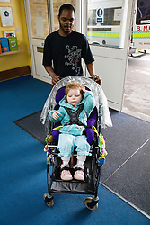 Child with physical disability arriving at school in a pushchair,
