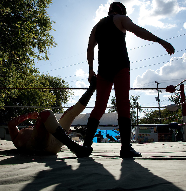 "Lucha Libre, where the air is hot, 100+ degrees in the shade in the shade, and so is the wrestling in San Antonio's Southside. With a community that is nearly 100% Hispanic the crowds here are not at all frightened by these masked men with bad attitudes and flare foe color. From all walks of life,  Luchadores don costumes and fly at each other for the entertainment of boisterous crowds that are encouraged to root for, taunt and shoot ""silly string"" at the wrestlers.  Referees seem to miss wrestling rule infractions and very bad sportsmanship.  (From Wikipedia) Lucha libre (Spanish for ""free wrestling"" or free fighting) is a term used in Mexico, and other Spanish-speaking countries referring to a form of professional wrestling involving varied techniques and moves.  Mexican wrestling is characterized by rapid sequences of holds and moves, as well as 'high-flying moves', some of which have been adopted in the United States, and colorful masks. Photo by and copyright 2009, Lance Cheung"