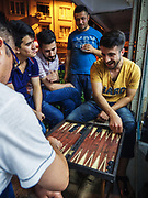 Mehmet plays backgammon with his boss. Mehmet, 23, has worked in barbershops in Istanbul's working-class outskirts since he was 7.