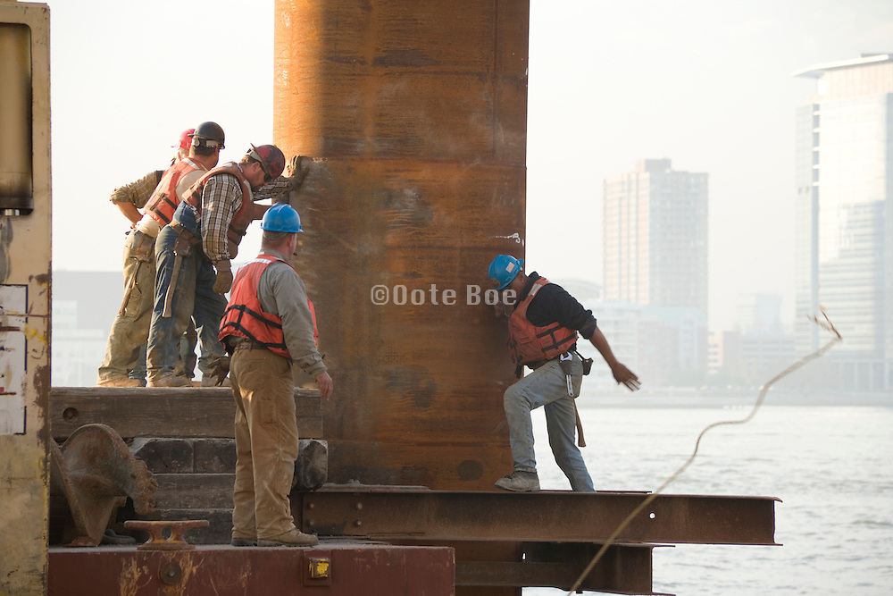 construction workers maneuvering a large steel column in place