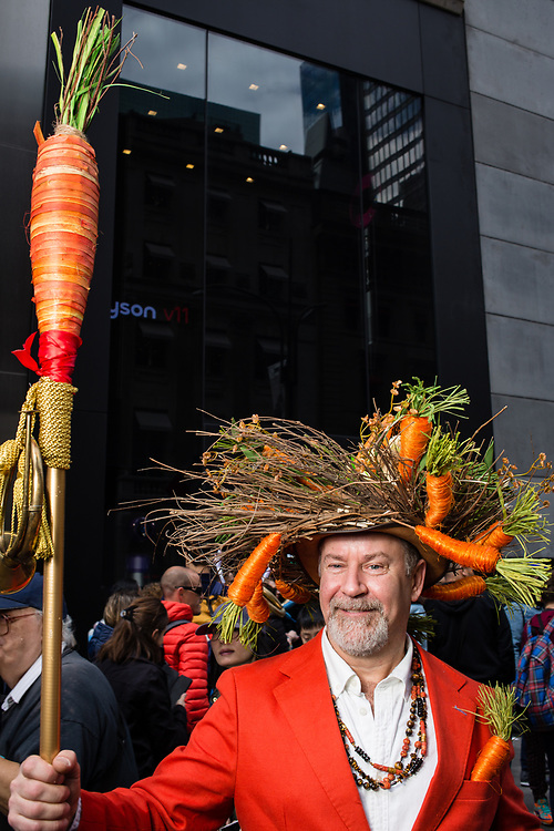New York, NY - 21 April 2019. A man with a hat festooned with carrots carries an oversized carrot on a pole at the Easter Bonnet Parade and Festival on New York's Fifth Avenue.