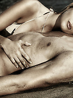 Sensual dramatic closeup of a couple lying together on sand at the beach. Black and white sepia toned.