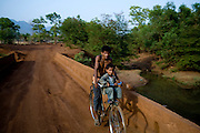 A villager takes his child to a make-shift school through  a village that has been heavly mined for chromite. Sukinda, Orissa, India...