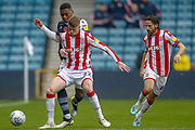 Millwall defender Mahlon Romeo (12) is tackled by Stoke City midfielder Sam Clucas (22), Stoke City midfielder Joe Allen (4), during the EFL Sky Bet Championship match between Millwall and Stoke City at The Den, London, England on 26 October 2019.