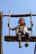Girl swinging on a wooden ferris wheel in the Gorkha region of Nepal.