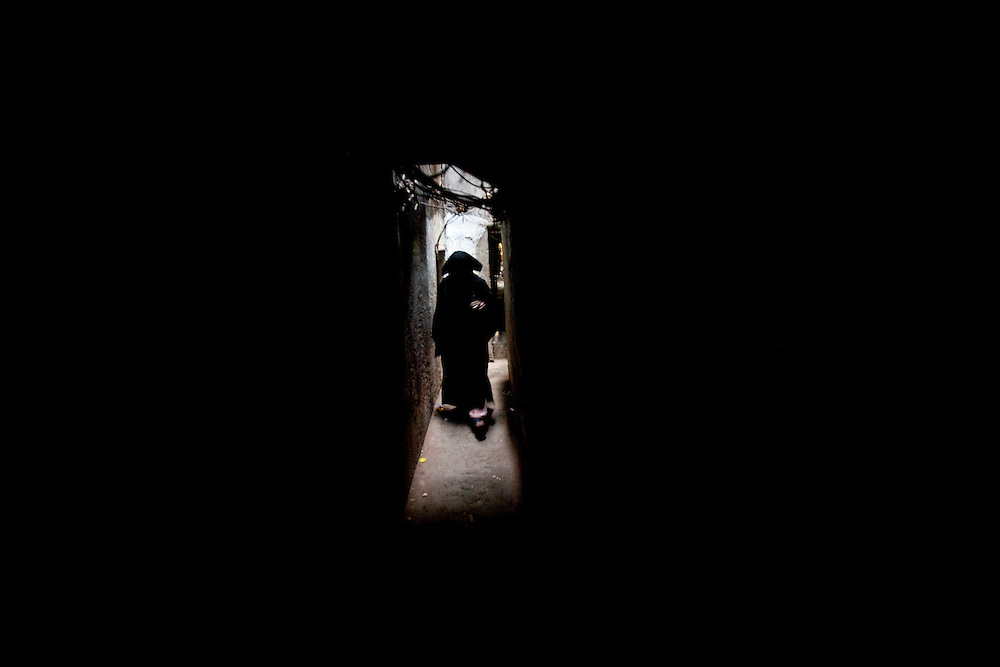 A burkha clad women wlaks through a dark alley in Razzaq chawl at the Behrampada area, in Mumbai, India, on Tuesday February 11, 2009.