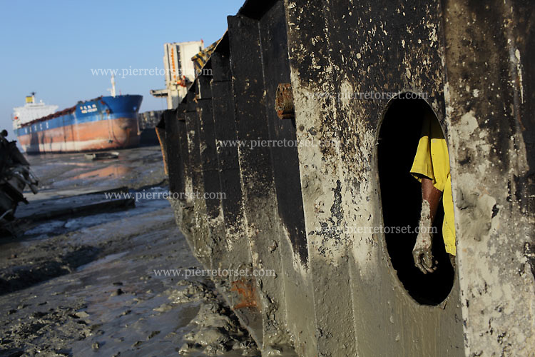 A worker removing some mix of mud and fuel residues. Using a shovel as much as his hands, he is lighting the ship part, making it easier to bring it closer to the beach by using a powerful winch.