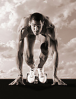 Sprinter crouching in starting blocks, portrait (B&W sepia)<br /> (digital composite)