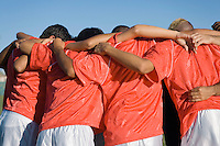 Soccer team in huddle back view