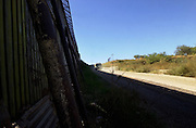 The U. S. and Mexico border wall, monitored by a U. S. Border Patrol agent, stretches between Nogales, Arizona, USA, and Nogales, Sonora, Mexico.