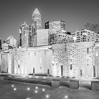 Charlotte at night black and white photo with Romare Bearden Park water wall and downtown Charlotte buildings. Charlotte is in North Carolina in the Eastern United States.