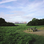 Fiddler's Ferry power station in Widnes on the river Mersey as seen from Wigg Island, Runcorn, with a picnic table in the foreground. The Mersey is a river in north west England which stretches for 70 miles (112 km) from Stockport, Greater Manchester, ending at Liverpool Bay, Merseyside. For centuries, it formed part of the ancient county divide between Lancashire and Cheshire.