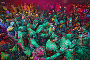 People covered in color sitting together and celebrating braj holi, the festival of colors, during the event of Samaaj where people of village Barsana and Nandgaon sit together and throw colors on each other.