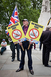 © Licensed to London News Pictures. 01/06/2013. London, UK. A British National Party (BNP) supporter holds anti-Muslim signs at a demonstration that was disrupted by Unite Against Fascism members who broke through a police cordon during protests by both groups in central London today (01/06/2013). The BNP protest was held in response to the killing of Drummer Lee Rigby, who died after an attack in Woolwich where religious extremism may have been the motive. Photo credit: Matt Cetti-Roberts/LNP