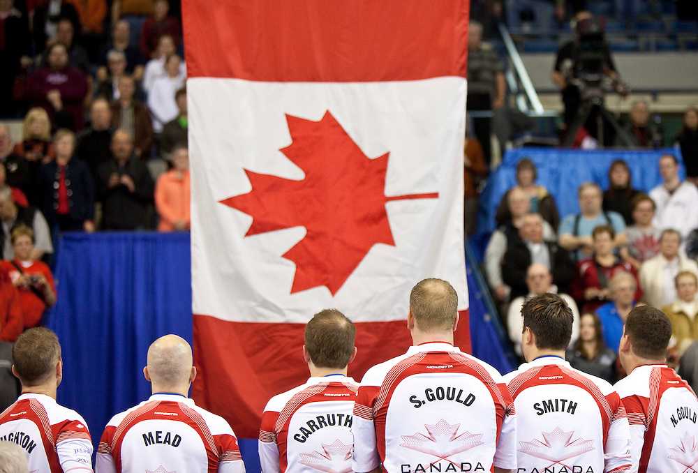 The Canadian team watch as the maple leaf is raised following their victory over Scotland in the gold medal game at the Ford World Men's Curling Championships in Regina, Saskatchewan, April 10, 2011.<br /> AFP PHOTO/Geoff Robins