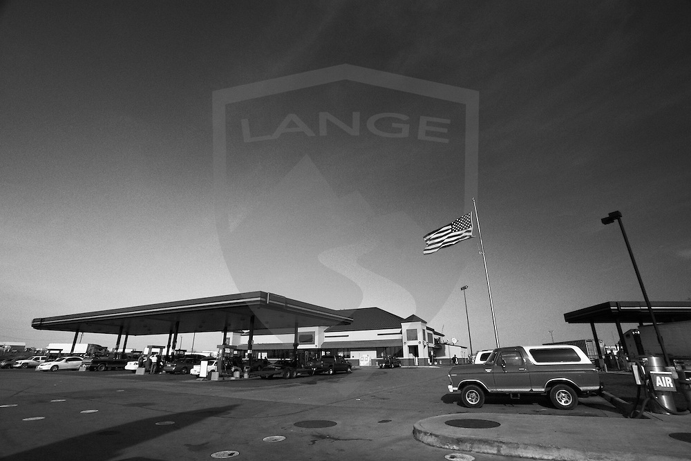 american gas station travel center with flag flying high, weatherford, oklahoma, usa, horizontal, copy space, black and white, wide angle