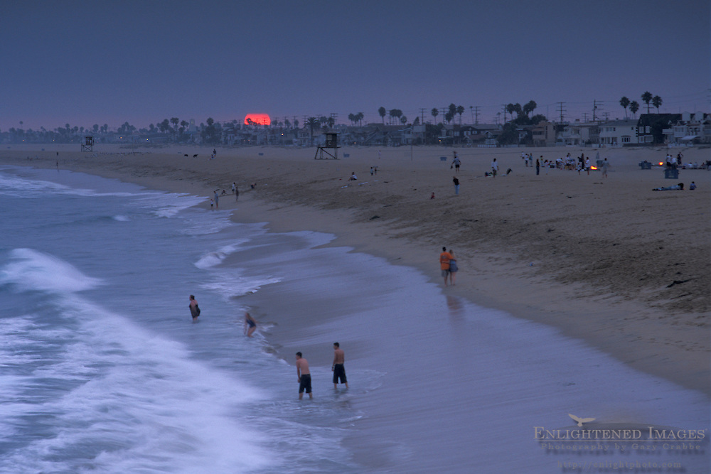 People wade in ocean surf at sunset below evening fog, near Balboa Pier, Balboa Island, Newport Beach, California