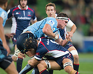 Kane Douglas (Waratahs) is tackled hard by Jarrod Saffy (Rebels) during the Round 15 match of the 2013 Super Rugby Championship between RaboDirect Rebels vs HSBC Waratahs at AAMI Park, Melbourne, Victoria, Australia. 24/05/0213. Photo By Lucas Wroe
