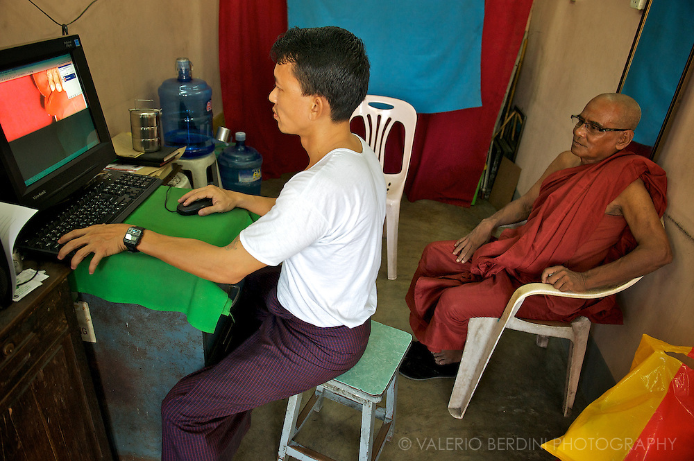 "Photographer editing a monk's passport photo with photoshop. Monks are expected to provide a living example for the laity and to serve as a ""field of merit"" for lay followers."