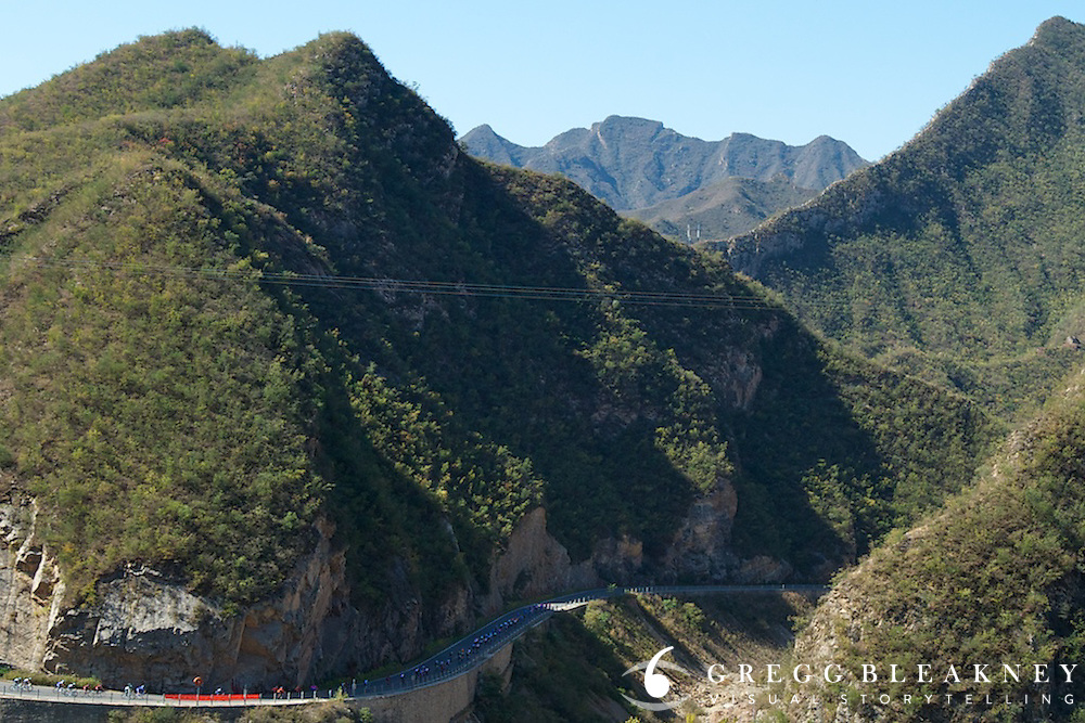 The peloton rolls through the mountains on the outskirts of Beijing.