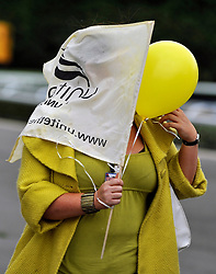 KEMPTON RACECOURSE. SURREY. A woman hides her face from the camera. Members of Unite and BA crew leave a union meeting at Kempton Racecoure in Surrey on the 6th September 2010. Union members were asked to wear the colour yellow and a decision was taken to ask the TUC for a Ballot calling for strike action for christmas. 06 SEPT 2010. STEPHEN SIMPSON ..