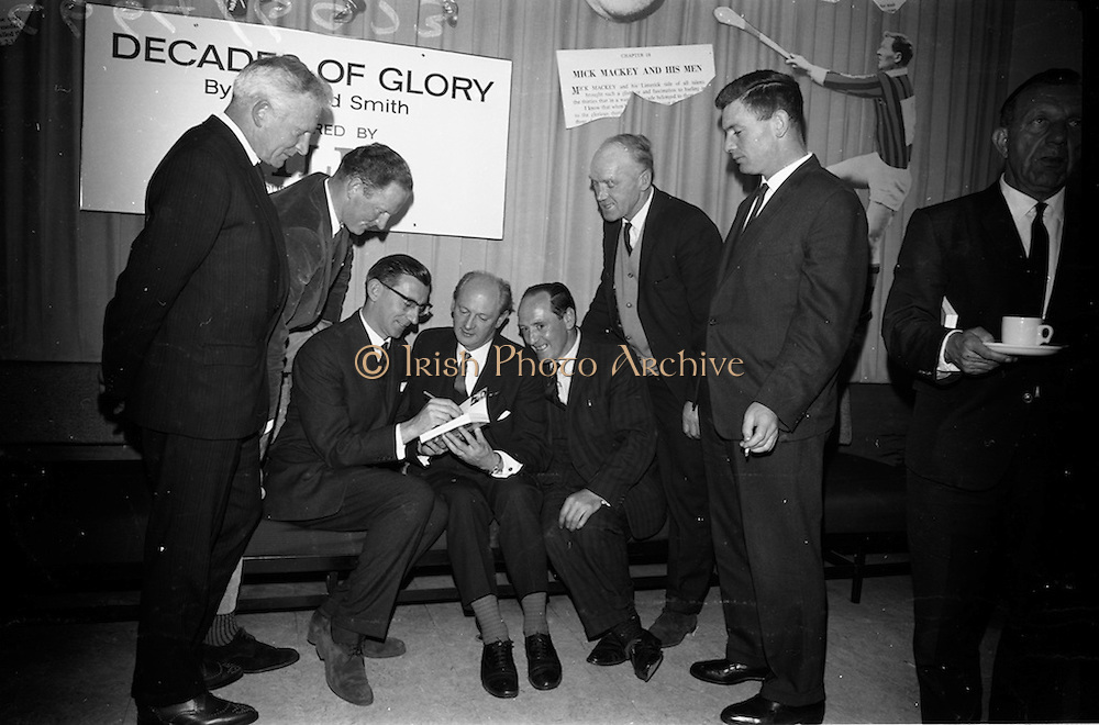 """17/05/1966<br /> 05/17/1966<br /> 17 May 1966<br /> Book reception for """"Decades of Glory: A Comprehensive History of the National Game"""" by Raymond Smith.<br /> This reception was held in the offices of W.D. & H.O. Wills to honour the well known author and journalist, Raymond Smith. His book on the history of Hurling (""""Decades of Glory"""") has just been published with the assistance of Wills of Dublin and Cork and the Central Council of the G.A.A.<br /> Picture shows (from left to right): Sean Duggan (Galway), Billy Rackard (Wexford),  Raymond Smith (autographing his book), Mr. Jack Lynch (at the time he was Minister for Finance), Jimmy Langton (Kilkenny), John Keane (Waterford), and Jimmy Smith (Clare)."""